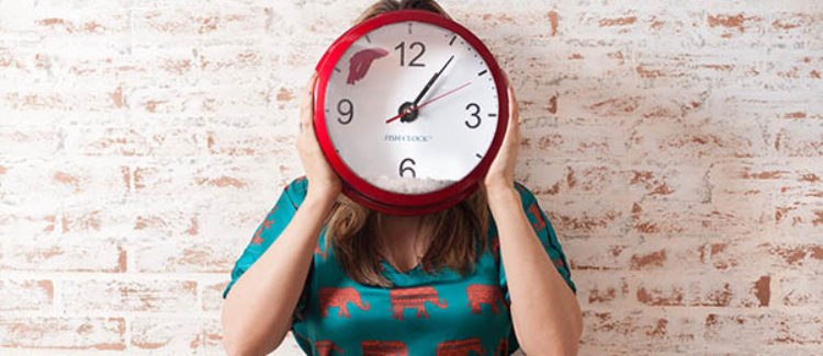 Woman Holding Clock Over Face